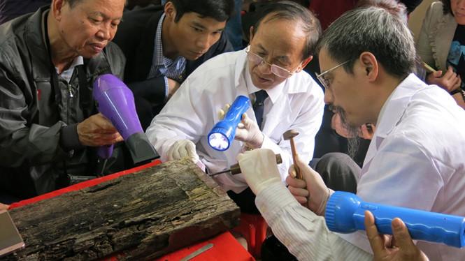 PGS-TS Nguyễn Lân Cường (giữa) cùng các chuyên gia tiến hành cạo lớp sơn ta để tìm thẻ tre trong tấm ván địa của quách.