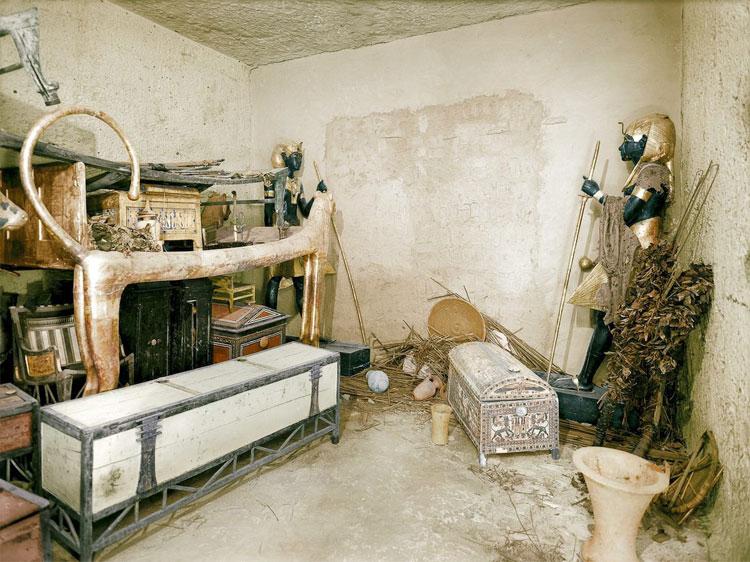 Một chiếc giường sư tử mạ vàng, rương quần áo và những vật dụng khác trong phòng.