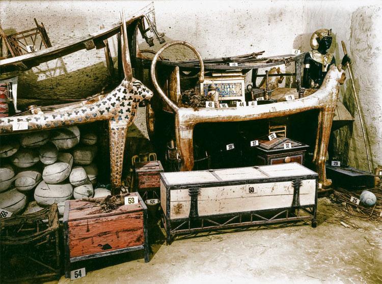 Một chiếc giường sư tử mạ vàng và rương quần áo cùng những đồ vật khác trong phòng.