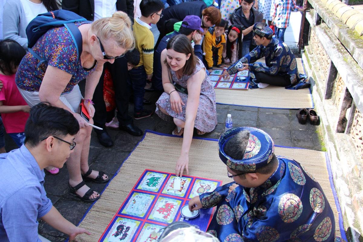 Nhiều du khách thấy trò bài vụ thú vị nên cũng tham gia chơi.