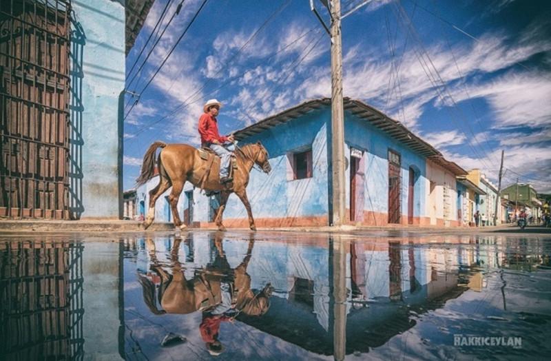 Sau cơn mưa, hình ảnh một khu phố phản chiếu một cách hoàn hảo xuống mặt nước mưa đọng lại trên đường.