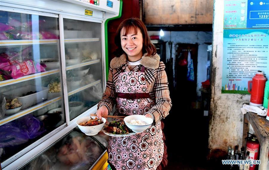 Cô Qing Ningling, chủ một quán trọ địa phương, chuẩn bị bữa trưa sau khi đón khách du lịch tới làng.