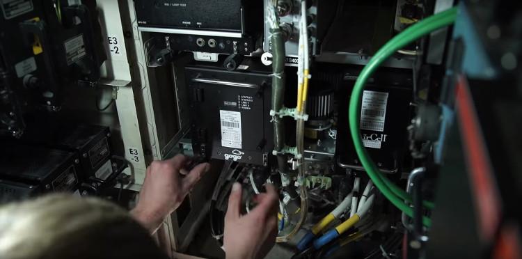 Một nhân viên kỹ thuật đang lắp đặt khối kết nối vệ tinh lên máy bay Boeing 747.
