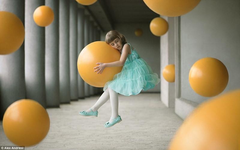 Bức ảnh đầy nghệ thuật về một bé gái ôm quả bóng lơ lửng trong không trung.