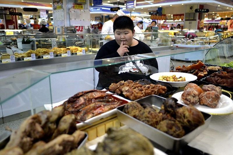 Ảnh chụp cậu bé Li Hang, 11 tuổi, người Cáp Nhĩ Tân, Trung Quốc tại một cửa hàng bán đồ ăn.