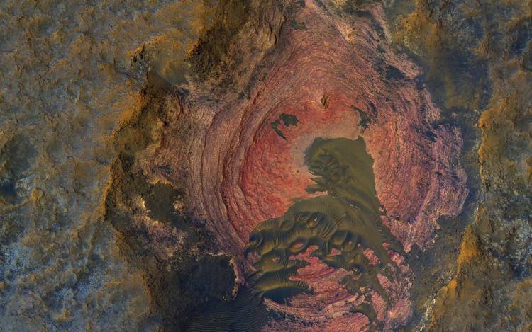 Một nền đá đầy màu sắc ở Sao Hỏa bao bọc xung quanh một cồn cát nhỏ nằm ở giữa.