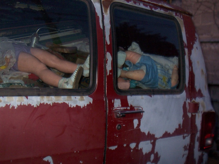 Lớp sơn đỏ bị tróc loang lổ như máu, bên trong là những con búp bê nằm ngổn ngang