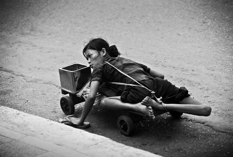 Một người tàn tật đi ăn xin dọc theo vỉa hè Sài Gòn, 1980.