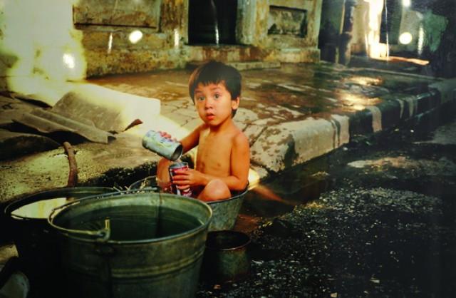 Em bé ngồi tắm trong chậu trên vỉa hè Hà Nội 1984.