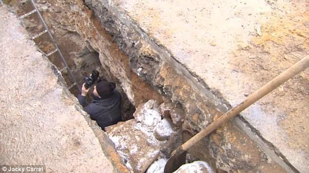 Nhà khảo cổ đang chụp hình hầm ngầm.