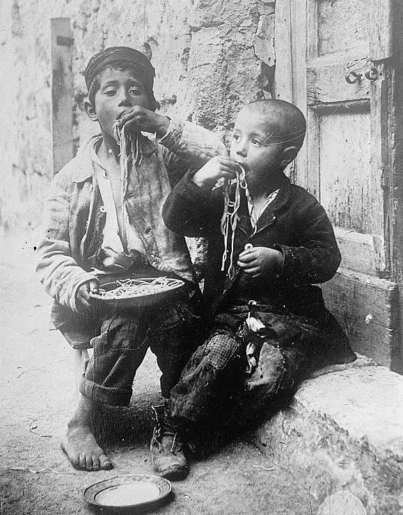 Hai đứa trẻ ngấu nghiến món mỳ Ý được chụp vào năm 1900.