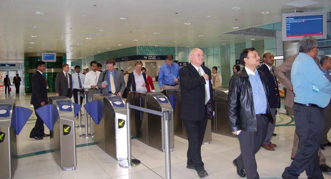Hành khách đưa vé vào khe có mũi tên trên cổng soát vé.