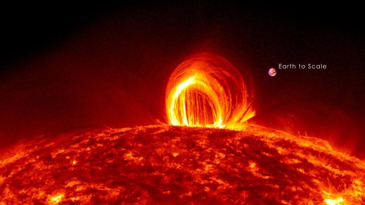 Vòng lửa trên bề mặt Mặt Trời, quả bóng tròn nhỏ bên cạnh kia chính là Trái Đất của chúng ta.