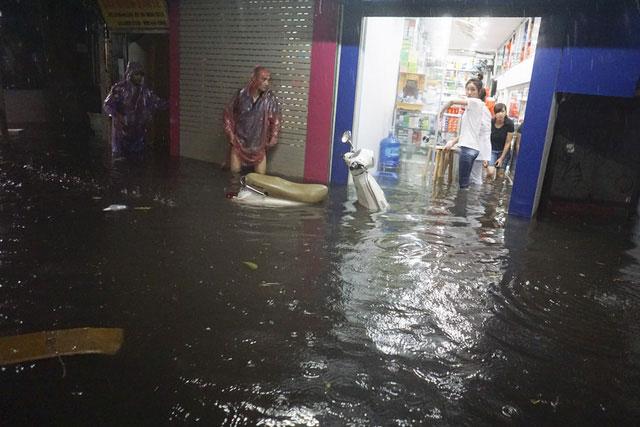 Nước tràn vào một hiệu thuốc, các nhân viên tại đây phải vất vả chạy hàng.