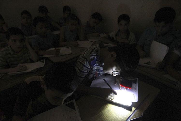 Vì thiếu điện, một học sinh đã dùng đèn pin để học bài.