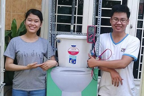 """Tín và Thanh bên cạnh mô hình """"Máy phát điện mini và pin tạo điện từ nước tiểu""""."""