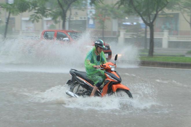 Người đi xe máy chật vật di chuyển qua biển nước tại khu vực đường Mễ Trì (quận Từ Liêm)