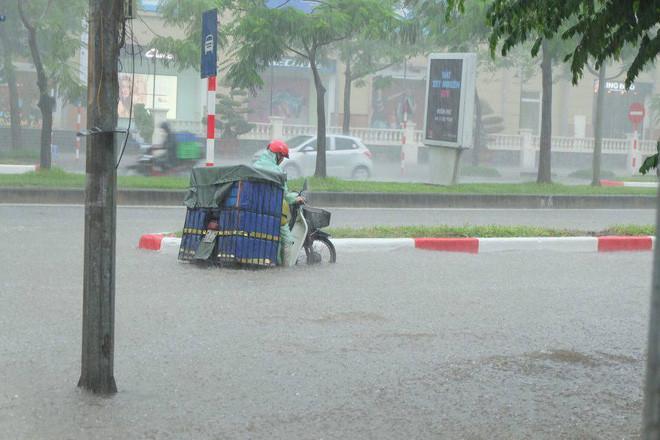 Một chiếc xe máy chở hàng bị chết máy giữa mưa lớn