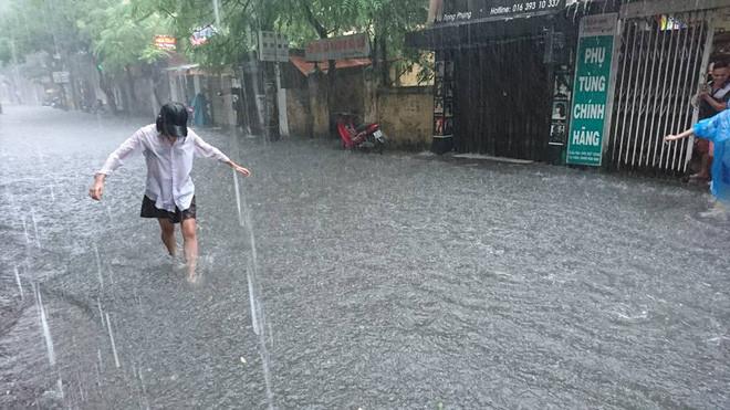 Đường Vũ Trọng Phụng (Thanh Xuân) nước dâng cao, một cô gái dầm mưa lội qua đoạn đường ngập.