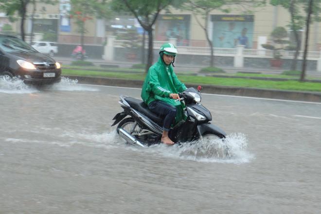 Một tài xế GrabBike đi chân không lái xe qua đoạn đường ngập sâu