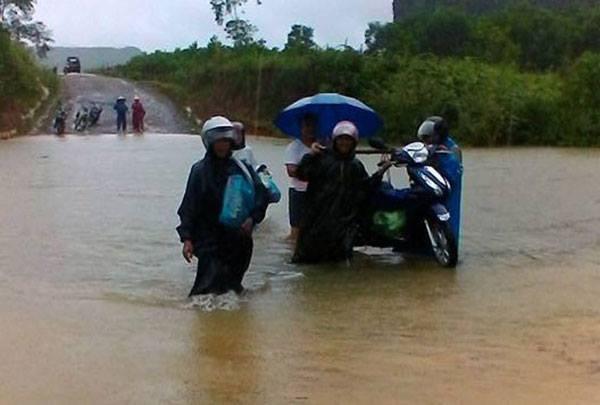 Người dân phải khiêng xe máy qua đoạn đường ngập.