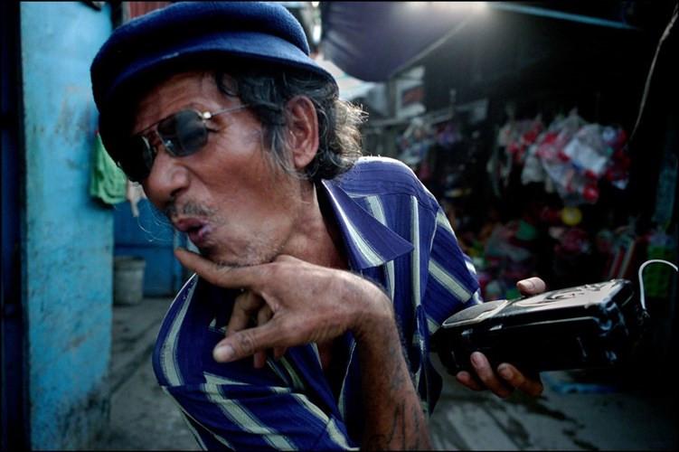 Một người đàn ông trung niên cầm máy nghe nhạc, ăn mặc kiểu Tây
