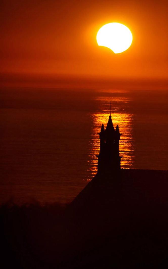 """Trong ảnh, ngôi nhà thờ Saint-They (Pháp) huyền ảo khi nhật thực """"ghé thăm"""" lúc hoàng hôn"""