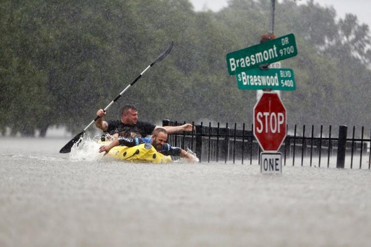Hai người chèo thuyến cố gắng chống lại dòng nước lũ ở phố Braeswood, Houston.