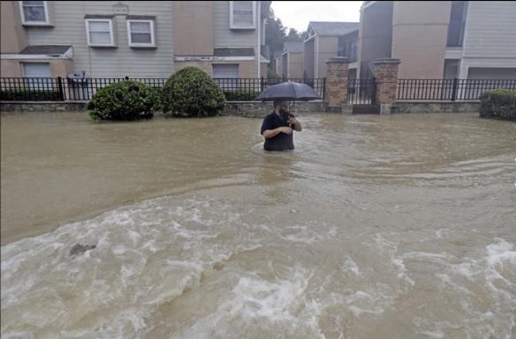 Một người dân đang lội giữa dòng lũ.