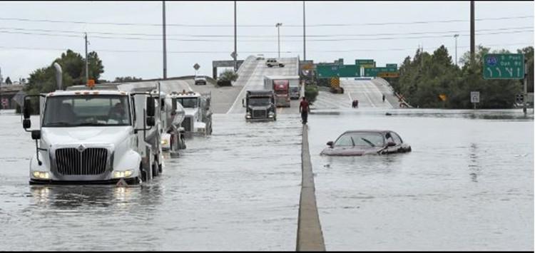 Xe cộ cố gắng di chuyển trong dòng nước lũ.