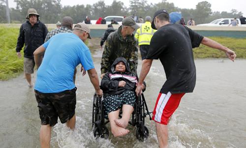 Một cụ bà trên xe lăn được giải cứu khỏi nước lũ ở đông Houston ngày 28/8.