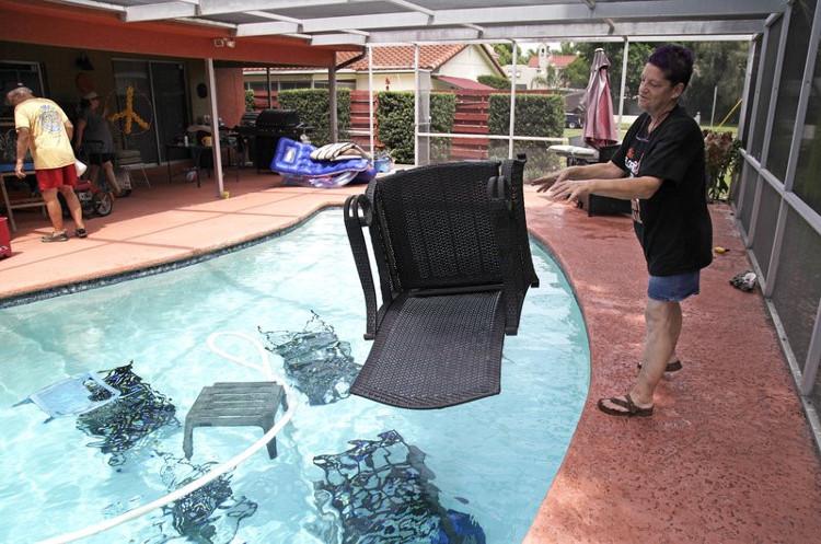 Một cư dân ở Gulfport, Florida ném đồ nội thất vào bể bơi để tránh các đồ vật này bị bão thổi bay