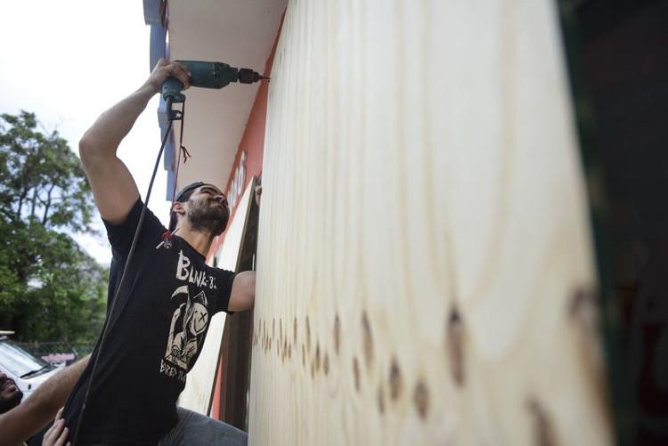 Một người dân đang gia cố cửa sổ với các thanh gỗ ép.