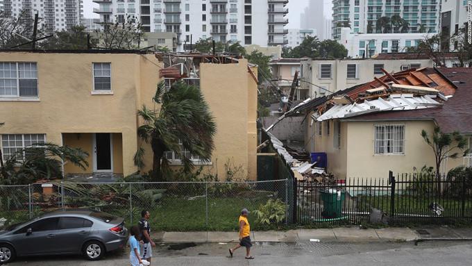 Cư dân đi quang qua những ngôi nhà ở Miami bị bão Irma làm tốc mái.