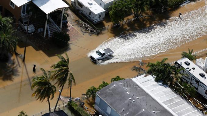 Xe ôtô của người dân đi qua con phố ngập nước lũ ở Key Largo ngày 11/9.