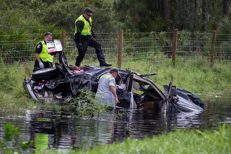 Cảnh sát đang cố gắng trục vớt một chiếc ôtô bị cơn bão nhấn chìm.