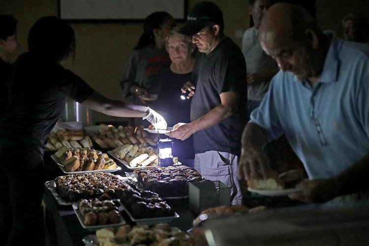 Trong ảnh, các vị khách trú bão tại một khách sạn đang dùng bữa trong cảnh cắt điện, với nguồn sáng từ một chiếc đèn nhỏ.