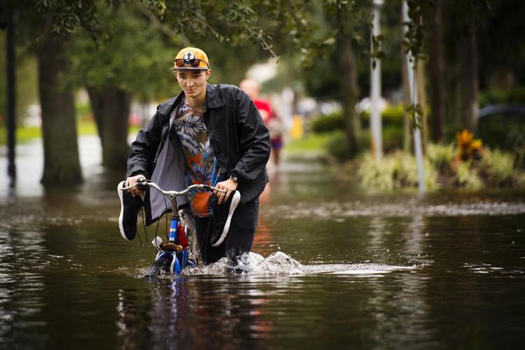 Người dân di chuyển khó khăn trong lụt lội tại Jacksonville.