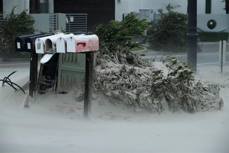 Trong ảnh, nhà cửa, cây cối và các hòm thư bị phủ mờ do bão mang cát từ bãi biển Pompano Blown vào.