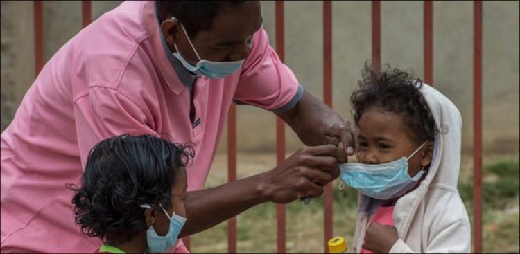 Nhân viên y tế đeo khẩu trang cho các em nhỏ ở Madagascar.