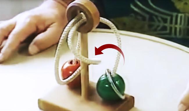 Thiết bị gồm trục gỗ, dây thừng, hai viên bi và một chiếc vòng.