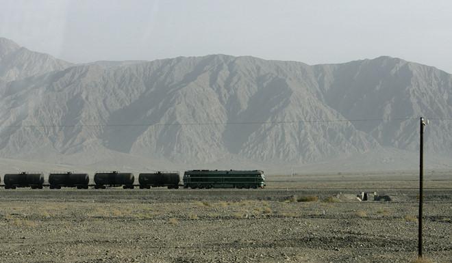 Một đoàn tàu chạy ngang dãy núi Thiên Sơn ở ngoài rìa sa mạc Taklimakan ở Tân Cương.
