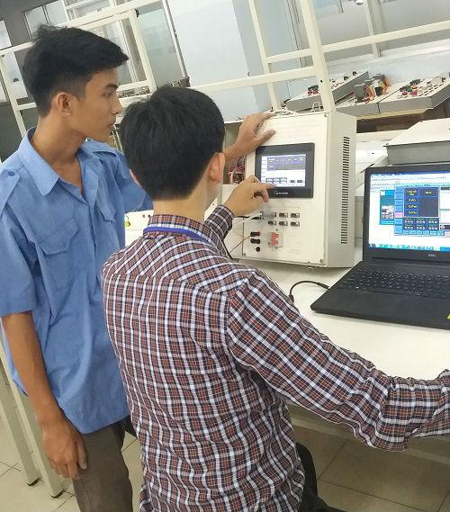 Hai sinh viên đang thử nghiệm mô hình hệ thống tại phòng thí nghiêm của trường
