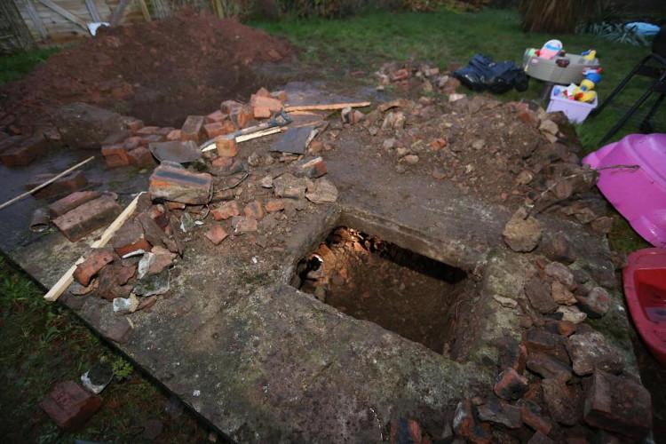 Cái hầm nằm bên dưới một nắp hố ga bằng bê tông.