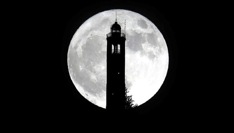 Siêu trăng mọc từ sau ngọn hải đăng ở San Maurizio, Italy.