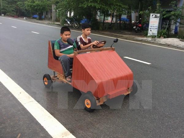 Em Lê Thiên Ân điều khiển chiếc xe ô tô có khung bằng gỗ, chạy bằng nguồn điện ắc quy vừa mới chế tạo.