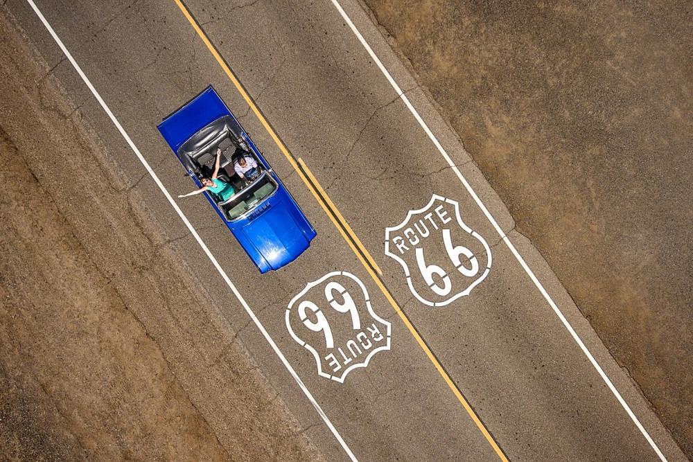 Cặp đôi ngồi trên chiếc Ford Mustang Convertible di chuyển dọc đường Route 66 ở Mỹ.