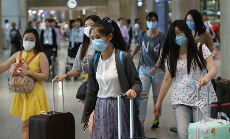 Khách du lịch sử dụng khẩu trang phòng dịch cúm lây lan tại sân bay.