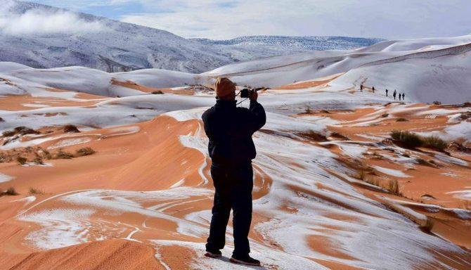 Một nhiếp ảnh gia đang chụp ảnh tuyết rơi trên sa mạc.