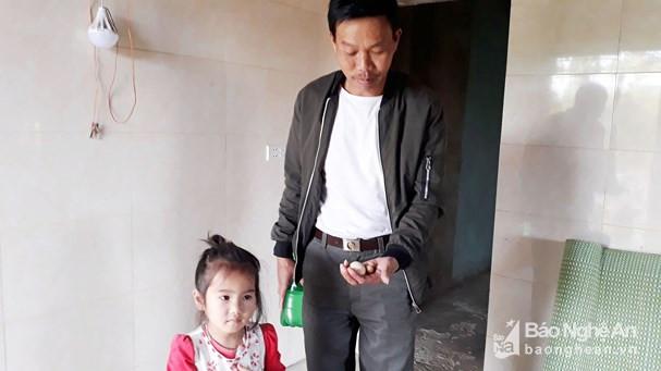 Ông Nguyễn Xuân Triều và 2 quả trứng nhỏ xíu. Ông cho rằng đó là trứng gà trống.